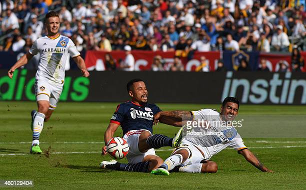 Charlie Davies of the New England Revolution gets tripped by A J DeLaGarza the Los Angeles Galaxy as Robbie Rogers looks on during the 2014 MLS Cup...