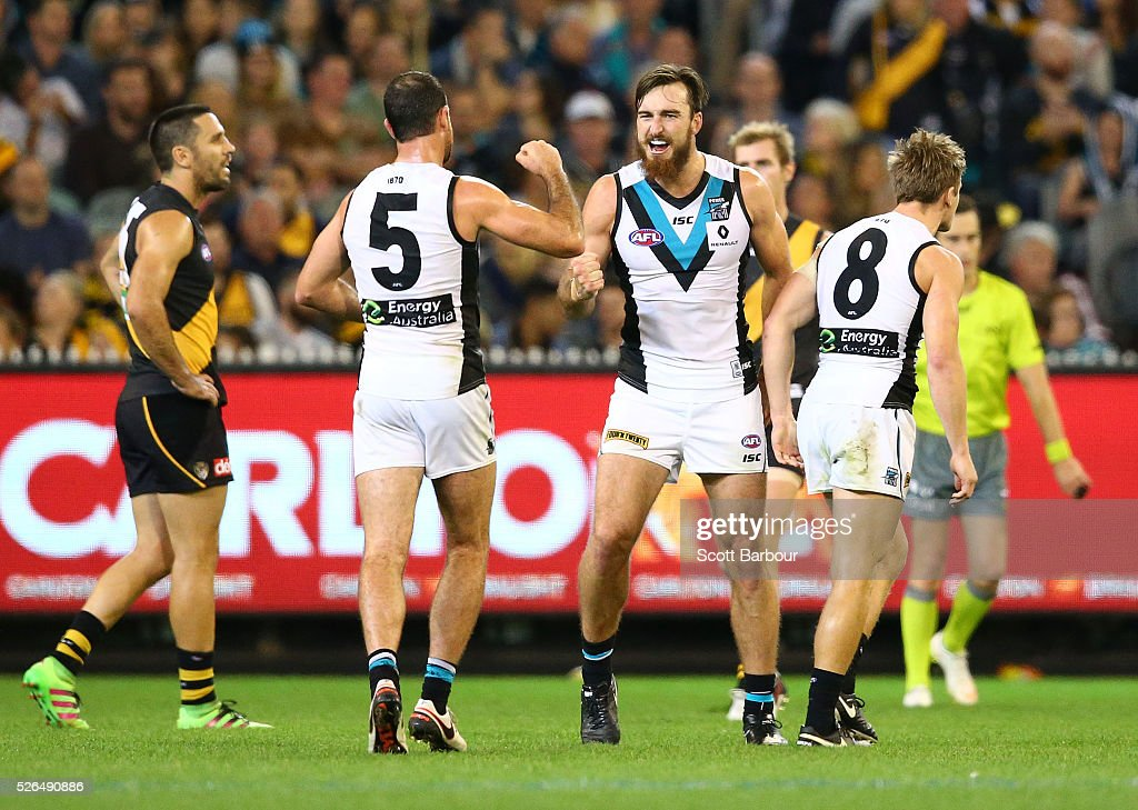 Charlie Dixon of the Power celebrates after kicking a goal as Troy Chaplin of the Tigers looks on during the round six AFL match between the Richmond Tigers and the Port Adelaide Power at Melbourne Cricket Ground on April 30, 2016 in Melbourne, Australia.
