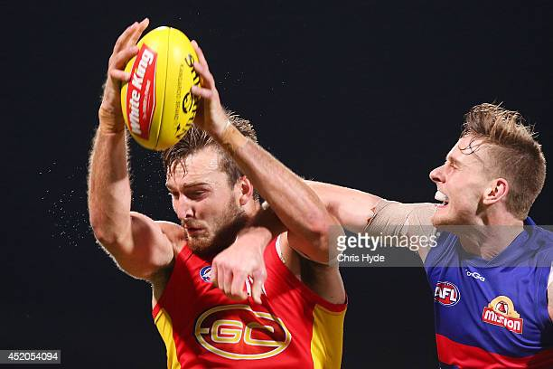 Charlie Dixon of the Suns has a mark spoiled by Jordan Roughead of the Bulldogs during the round 17 AFL match between the Western Bulldogs and the...