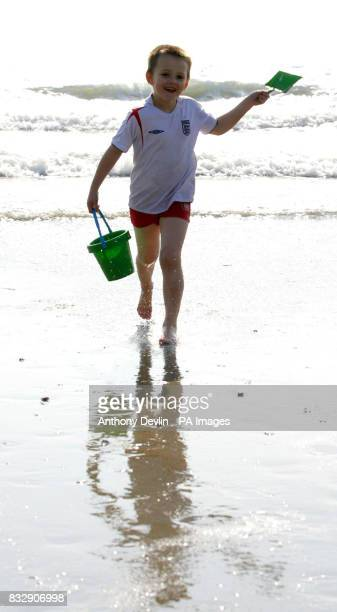 Charlie Gardner from Leicester collects water for a sandcastle on the beach at Looe Cornwall where holiday makers are enjoying the warm sunshine