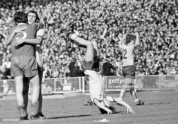 Charlie George of Arsenal does a forward roll whilst Ray Kennedy of Arsenal is hugged by Larry Lloyd of Liverpool after Arsenal's 21 victory over...