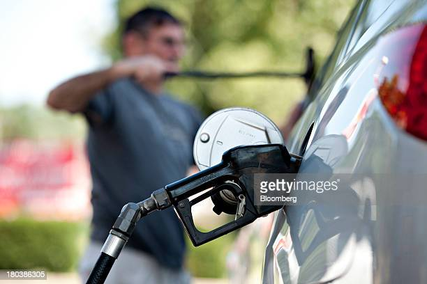 Charlie Gourd cleans his windshield while putting fuel in his vehicle at a Royal Dutch Shell Plc gas station in Peoria Illinois US on Wednesday Sept...