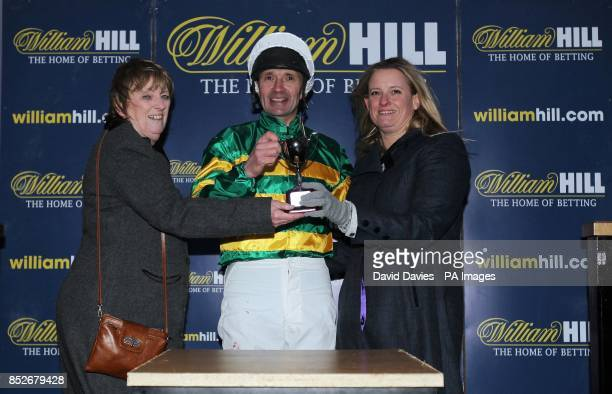 Charlie Hancock receives his prize after his victory in the fial of The William Hill Camel Derby at Chepstow Racecourse