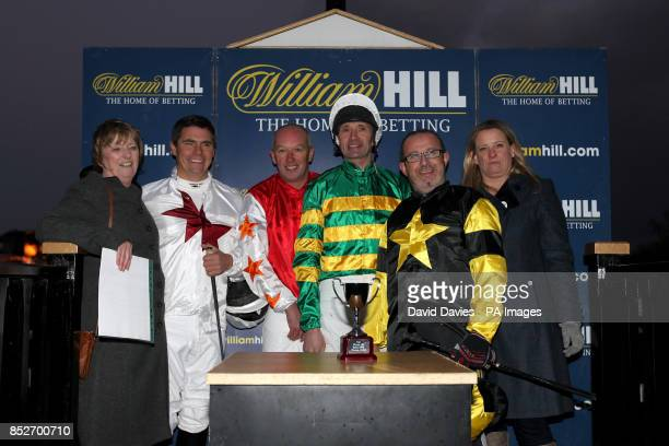 Charlie Hancock with fellow jockeys receives his prize after his victory in the final of The William Hill Camel Derby at Chepstow Racecourse
