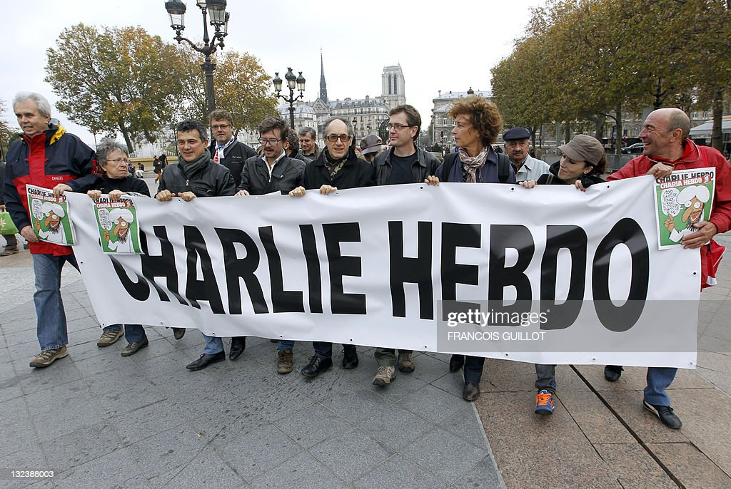 Charlie Hebdo culumnist Patrick Pelloux (3rdL), Charlie Hebdo cartoonist Luz (4thL), Charlie Hebdo editor-in-chief <a gi-track='captionPersonalityLinkClicked' href=/galleries/search?phrase=Gerard+Biard&family=editorial&specificpeople=7607358 ng-click='$event.stopPropagation()'>Gerard Biard</a> (C), Charlie Hebdo publisher and cartoonist Charb (4rd), editor-in-chief deputy Sylvie Coma (2rdR) and Charlie Hebdo cartoonist Catherine (2ndR) march behind a banner reading 'Charlie Hebdo', during a support rally for French satirical magazine Charlie Hebdo, in front of Paris townhall on November 6, 2011, a few days after the offices have been destroyed in a petrol bomb attack. The edition of the paper published, which was called Charia Hebdo - a play on the Islamic word sharia, was intended to 'celebrate' the victory of an islamist party in last month's Tunisian elections.