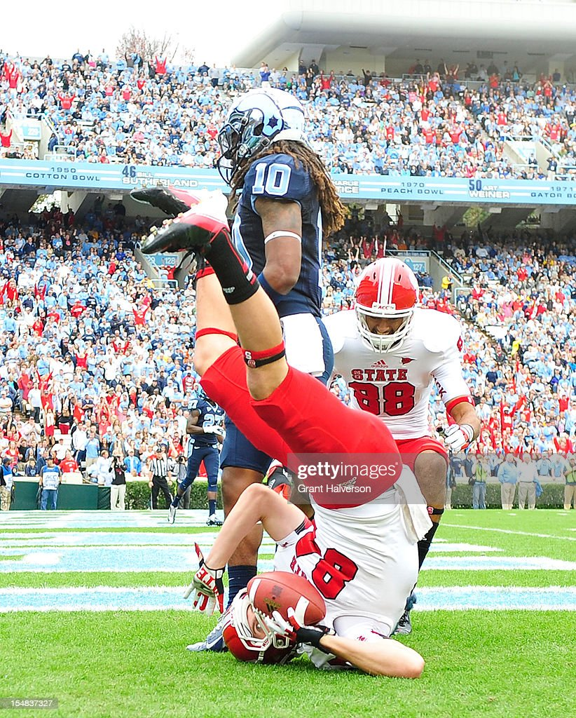Charlie Hegedus #84 of the North Carolina State Wolfpack makes an acrobatic touchdown catch against Tre Boston #10 of the North Carolina Tar Heels during play at Kenan Stadium on October 27, 2012 in Chapel Hill, North Carolina.