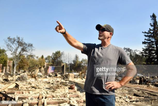 TOPSHOT Charlie Higgins speaks to his wife at their burned home in Santa Rosa California on October 12 2017 Hundreds of people are still missing in...