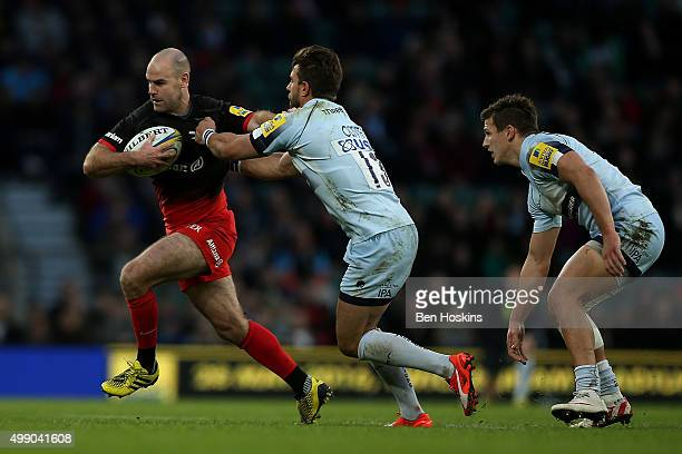 Charlie Hodgson of Saracens hand off the tackle of Wynand Oliver of Worcester during the Aviva Premiership match between Saracens and Worcester...