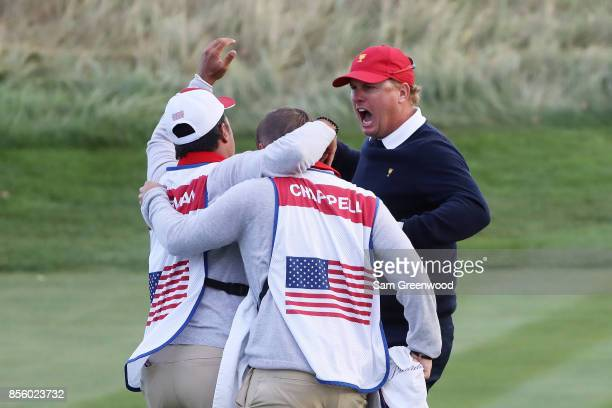 Charlie Hoffman of the US Team reacts after chipping in on the 17th hole during Saturday fourball matches of the Presidents Cup at Liberty National...