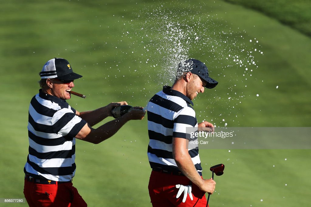 Charlie Hoffman sprays Daniel Berger of the U.S. Team with champagne after Berger defeated Si Woo Kim of South Korea and the International Team on the 17th hole 2&1 to give the U.S. Team the clinching point to win the Presidents Cup during Sunday singles matches at Liberty National Golf Club on October 1, 2017 in Jersey City, New Jersey.