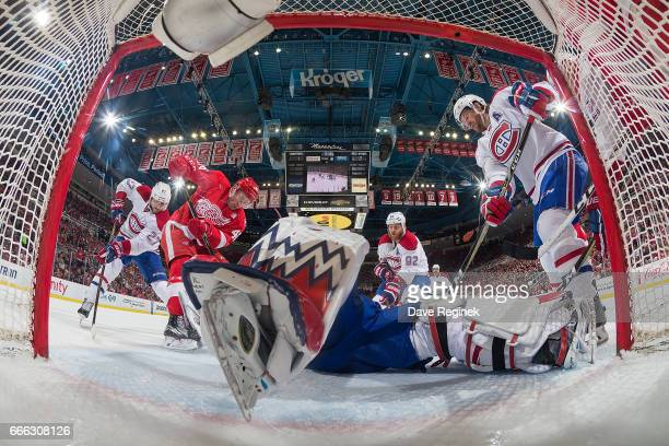 Charlie Lindgren of the Montreal Canadiens lays out on the ice to make a save as teammate Jeff Petry and Ben Street of the Detroit Red Wings look for...