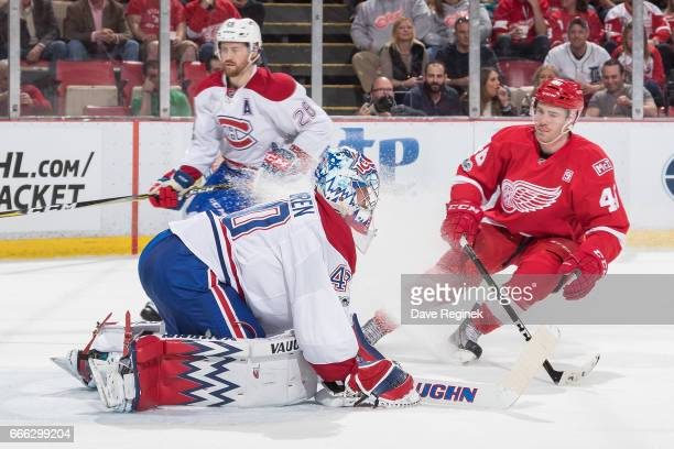 Charlie Lindgren of the Montreal Canadiens makes a saves as Ben Street of the Detroit Red Wings skates in for the rebound during an NHL game at Joe...
