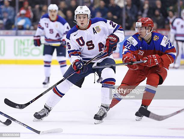 Charlie McAvoy of Team USA flips the puck ahead while being checked by Danil Yurtaikin of Team Russia during a preliminary game at the 2017 IIHF...