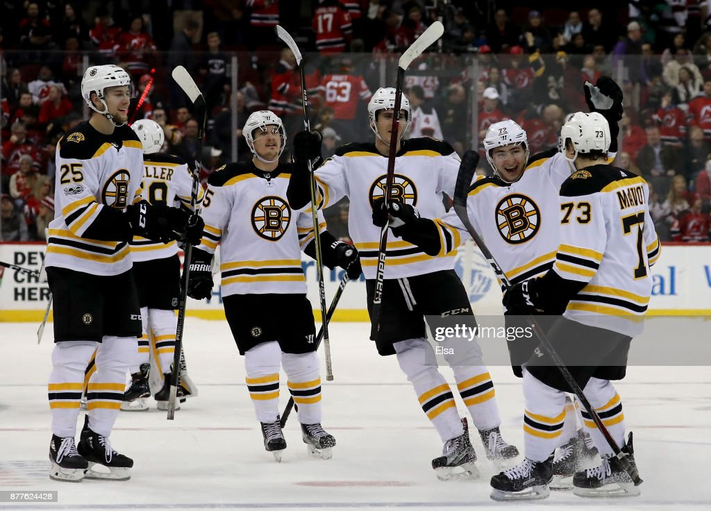 Charlie McAvoy #73 of the Boston Bruins is congratulated by Frank Vatrano #72 and the rest of his teammates off the bench after he scored to win the game in an overtime shootout against the New Jersey Devils on November 22, 2017 at Prudential Center in Newark, New Jersey.The Boston Bruins defeated the New Jersey Devils 3-2 in an overtime shootout.