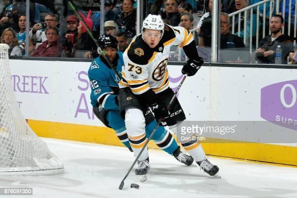 Charlie McAvoy of the Boston Bruins keeps the puck ahead of Joel Ward of the San Jose Sharks at SAP Center on November 18 2017 in San Jose California