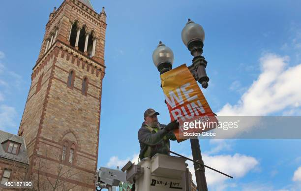 Charlie McCarthy hangs Boston Marathon banners near the finish line from a bucket truck