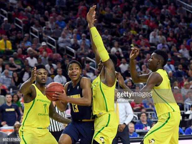 Charlie Moore of the California Golden Bears looks to pass under pressure from Jordan Bell Dylan Ennis and Chris Boucher of the Oregon Ducks during a...