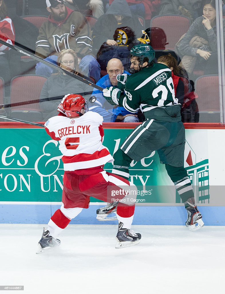 Charlie Mosey #28 of the Dartmouth College Big Green is checked by Matt Grzelcyk #5 of the Boston University Terriers as the puck pops in between them during NCAA hockey action at Agganis Arena on January 8, 2014 in Boston, Massachusetts.