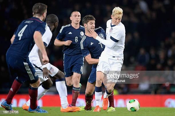 Charlie Mulgrewof Scotland tackles Brek Shea of the USA during the international friendly at Hampden Park on November 15 2013 in Glasgow Scotland