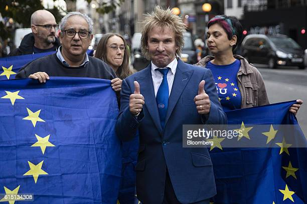 Charlie Mullins founder of Pimlico Plumbers Ltd center poses for photographers alongside proEU supporters outside the Royal Courts of Justice in...
