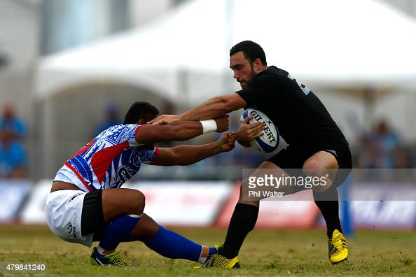 Charlie Ngatai of the New Zealand All Blacks is tackled by Johnny Leota of Manu Samoa during the International Test match between Samoa and the New...