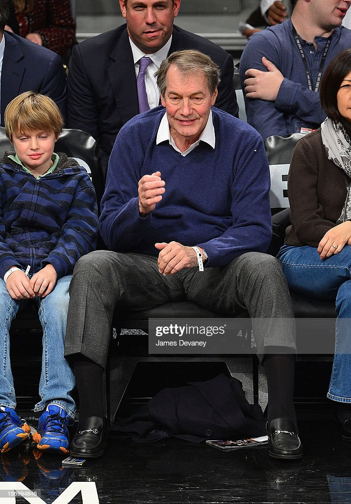 Charlie Rose and guest (L) attend the New York Knicks vs Brooklyn Nets game at Barclays Center on November 26, 2012 in the Brooklyn borough of New York City.