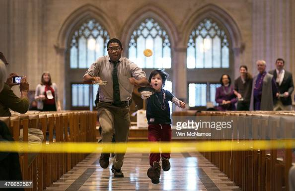 Charlie Savan competes in the Washington National Cathedral's Pancake Race with Rodrick Murray on Shrove Tuesday March 4 2014 in Washington DC Due to...
