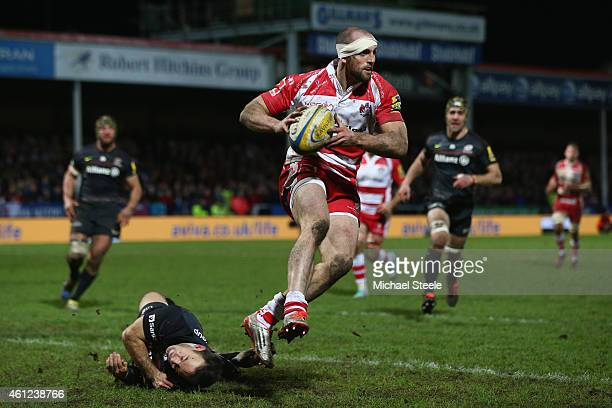 Charlie Sharples of Gloucester sidesteps the tackle of Neil de Kock of Saracens during the Aviva Premiership match between Gloucester Rugby and...