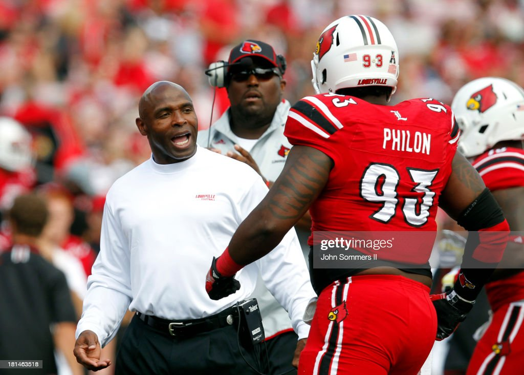 Charlie Strong head coach of the Louisville Cardinals talks with Roy Philon #93 of the Cardinal during their game against Florida International Panthers at Papa John's Cardinal Stadium on September 21, 2013 in Louisville, Kentucky.