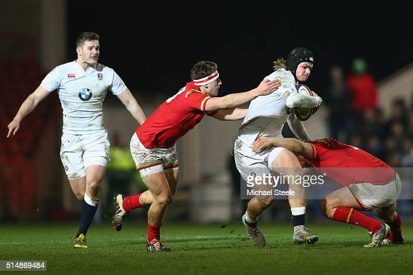Charlie Thacker of England U20 is held up by Harri Millard and Dafydd Hughes of Wales U20 during the Six Nations match between England U20 and Wales...