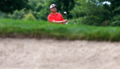 Charlie Wi of Korea watches his approach shot on the ninth hole during the first round of the Travelers Championship golf tournament at the TPC River...
