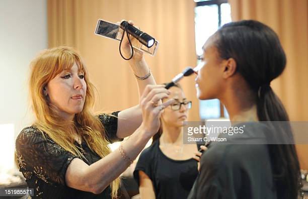 Charlott Tillbury prepares a model backstage ahead of the Sass Bide show on day 1 of London Fashion Week Spring/Summer 2013 at The Lindley Hall on...