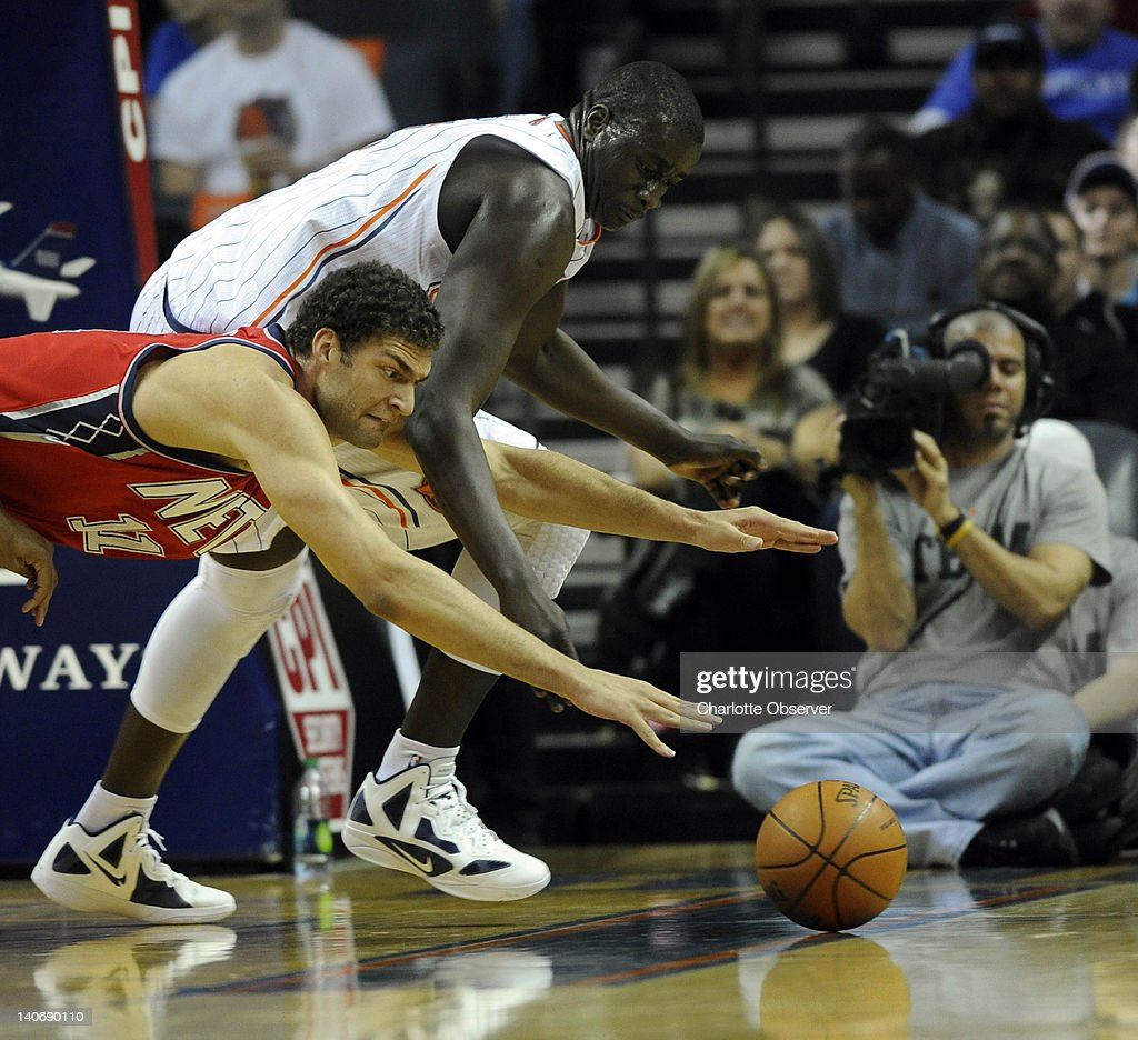 Charlotte Bobcats' DeSagana Diop (7) and New Jersey Nets' Brook Lopez (11) dive for a loose ball during the first half of their game at Time Warner Cable Arena on March 4, 2012, in Charlotte, North Carolina.