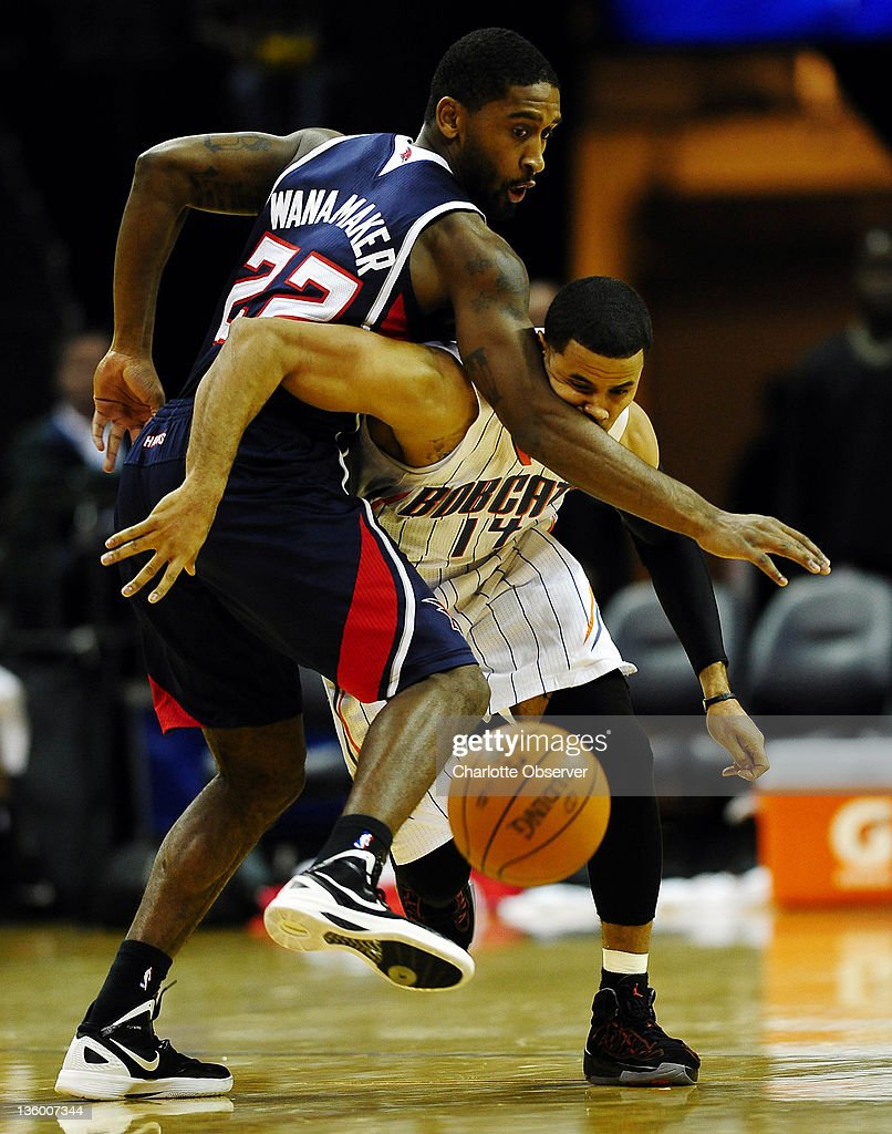 Charlotte Bobcats' D.J. Augustin (14) works to get past Atlanta Hawks' Brad Wanamaker (22) for a loose ball during the second half of their preseason game at Time Warner Cable Arena in Charlotte, North Carolina on Monday, December 19, 2011.