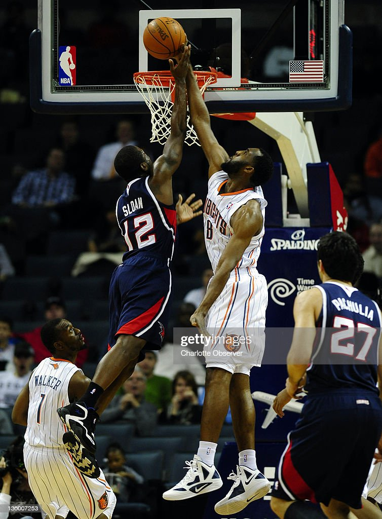 Charlotte Bobcats' D.J. White (8) blocks the shot of Atlanta Hawks' Donald Sloan (12) during the first half of their preseason game at Time Warner Cable Arena in Charlotte, North Carolina on Monday, December 19, 2011.