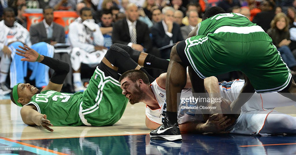 Charlotte Bobcats forward/center Byron Mullens fights to maintain control of a loose ball against Boston Celtics forward Brandon Bass (30) during first-half action at Time Warner Cable Arena in Charlotte, North Carolina, Monday, February 11, 2013.