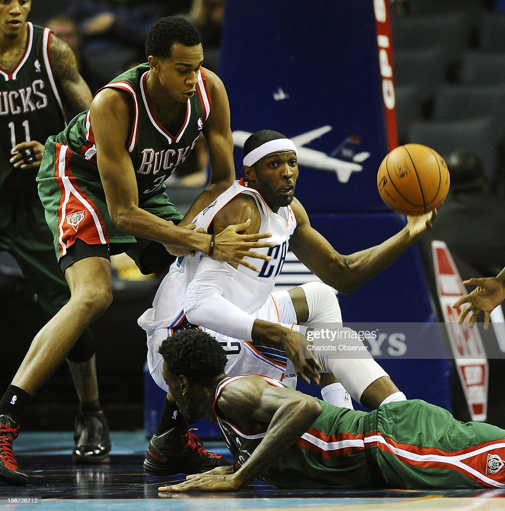 Charlotte Bobcats' Hakim Warrick (14) goes after a loose ball between Milwaukee Bucks' John Henson (31) and Larry Sanders (8) during the second half at Time Warner Cable Arena on Monday, November 19, 2012, in Charlotte, North Carolina. Charlotte won, 102-98.
