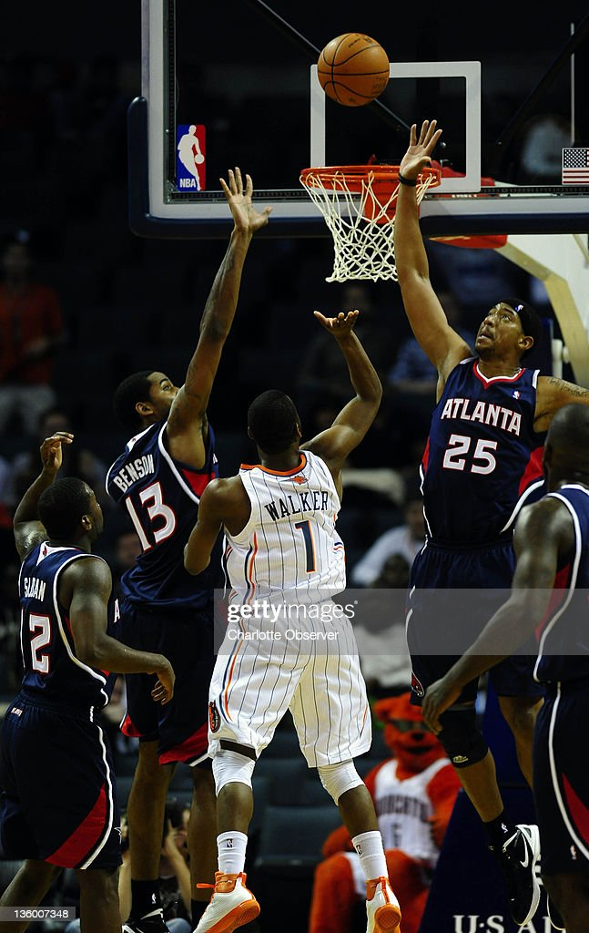 Charlotte Bobcats' Kemba Walker (1) floats a shot past Atlanta Hawks' Keith Benson (13) and Magnum Rolle (25) during the second half of their preseason game at Time Warner Cable Arena in Charlotte, North Carolina on Monday, December 19, 2011.