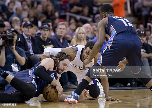Charlotte Bobcats power forward Josh McRoberts picks up a loose ball in front of Sacramento Kings power forward Derrick Williams before passing it to...