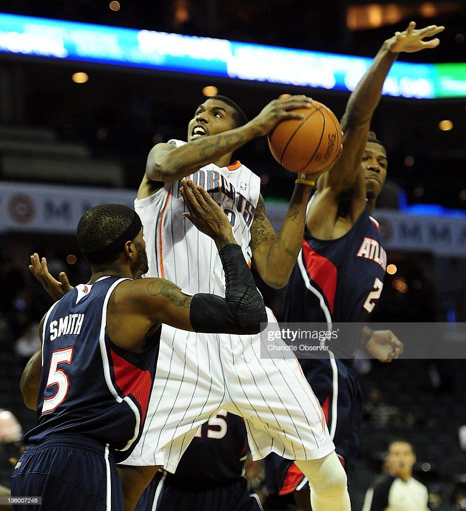 Charlotte Bobcats' Tyrus Thomas (12) drives in between Atlanta Hawks' Josh Smith (5) and Joe Johnson (2) during the first half of their preseason game at Time Warner Cable Arena in Charlotte, North Carolina on Monday, December 19, 2011.