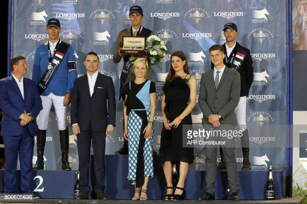 Charlotte Casiraghi poses on the podium during the 'Grand Prix Prince de Monaco' with equestrians Germany's Christian Ahlmann Italy's Alberto Zorzi...