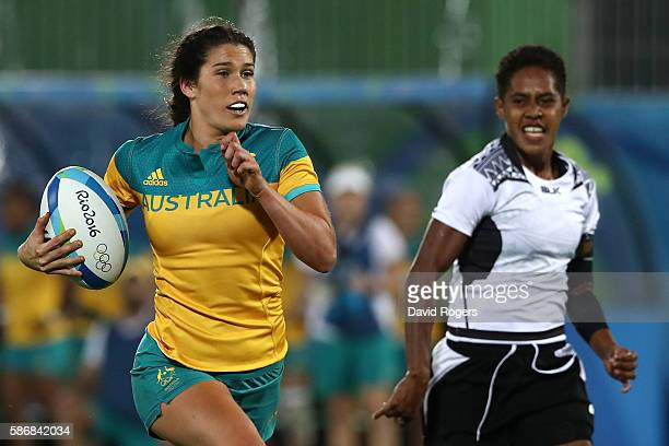 Charlotte Caslick of Australia runs with the ball to score a try under pressure of Luisa Tisolo of Fiji during a Women's Pool A rugby match between...