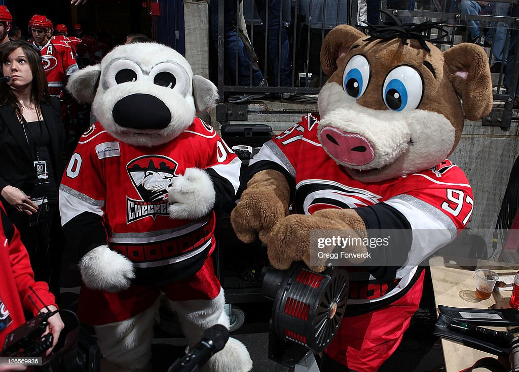 Charlotte Checkers mascot Chubby, and Carolina Hurricanes mascot Stormy sound the Hurricane warning siren prior to an NHL preseason game against the Winnipeg Jets on September 25, 2011 at Time Warner Arena in Charlotte, North Carolina.