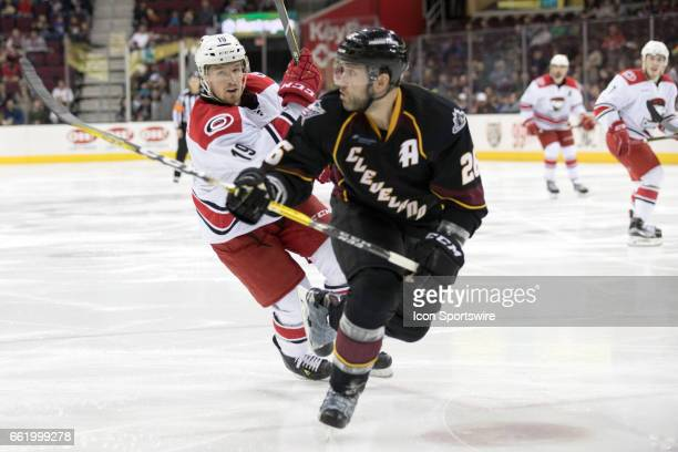 Charlotte Checkers RW Andrew Miller and Cleveland Monsters D Jaime Sifers follow the puck into the corner during the third period of the AHL hockey...