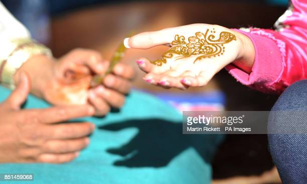 Charlotte Garner has a henna put on her hand at the Abu Dhabi Fan zone at a camp site for the British Grand Prix at Silverstone PRESS ASSOCIATION...