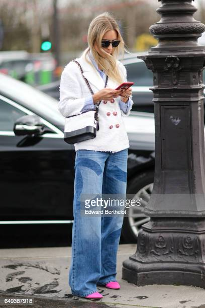 Charlotte Groeneveld wears sunglasses a Chanel white tweed jacket a Chanel bag blue jeans and pink shoes outside the Chanel show during Paris Fashion...