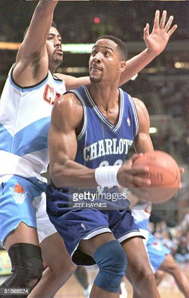 Charlotte Hornets Alonzo Mourning looks back at the basket as the Cleveland Cavaliers John Williams guards him 10 January during the second half of...
