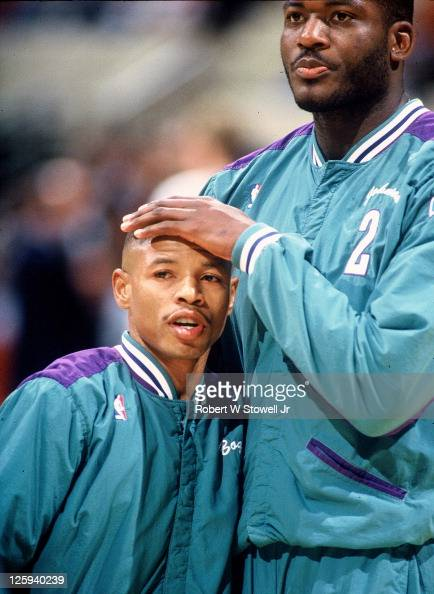 Charlotte Hornets duo of point guard Tyrone 'Mugsy' Bogues and forward Larry Johnson embrace during pregame introductions for a game against the...
