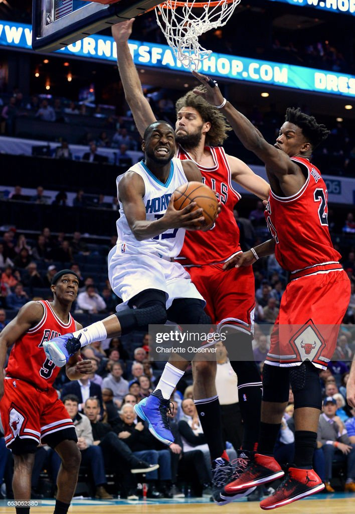 Charlotte Hornets guard Kemba Walker, left, drives to the basket for a shot attempt as Chicago Bulls center Robin Lopez, and forward Jimmy Butler, right, apply defensive pressure during second half action against the Chicago Bulls on Monday, March 13, 2017 at the Spectrum Center in Charlotte, N.C. Butler would block the shot attempt. The Bulls defeated the Hornets 115-109.