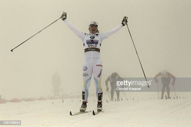 Charlotte Kalla of Sweden celebrates as she crosses the finish line to win the gold medal in the Ladies Cross Country Team Sprint race during the FIS...